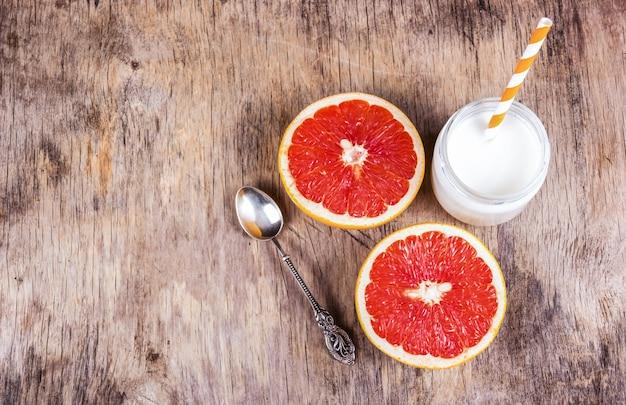 Twee helften van sappige grapefruit, vintage zilveren lepel en zelfgemaakte yoghurt op de oude houten achtergrond. kopieer ruimte.