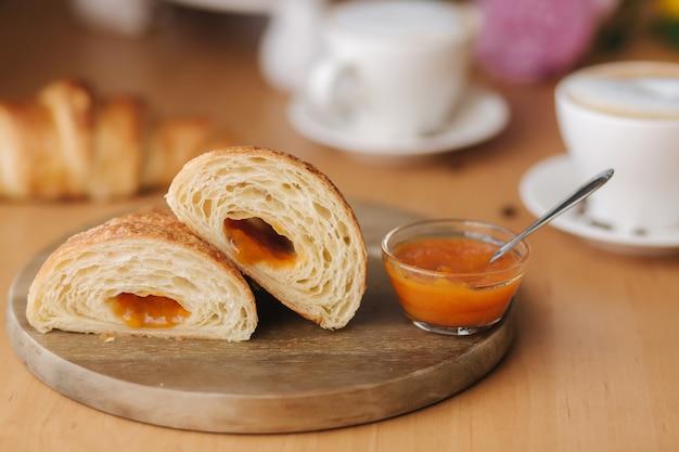 Twee helften van vers ontblootte croissant op houten bord met heerlijke zelfgemaakte abrikozenjam.