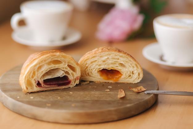 Twee helften van vers ontblootte croissant op houten bord met verschillende jam.