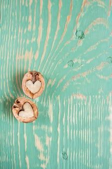 Twee helften walnoot als hart liggen op lichtgroene houten tafel met strepen en kronkelige vlekken.