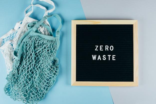 Twee herbruikbare katoenen zakken (netzakken) en prikbord met tekst zero waste