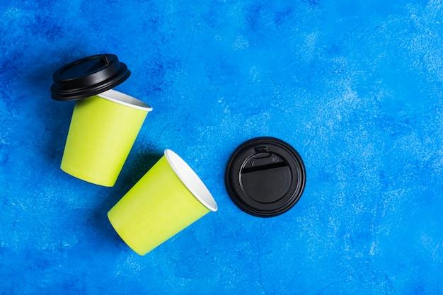 Twee herbruikbare koffiekopjes van groen papier met zwarte deksels