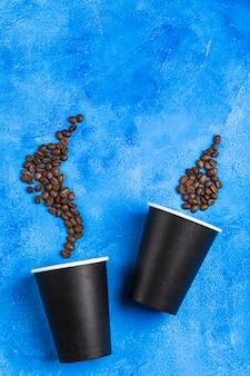 Twee herbruikbare koffiekopjes van zwart papier met koffiebonen.