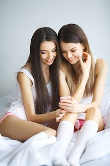 Twee hete meiden liggen op een bed en nemen een foto van zichzelf