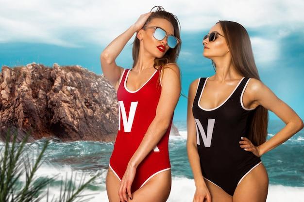 Twee hete meiden poseren op het strand in bodyzwempak