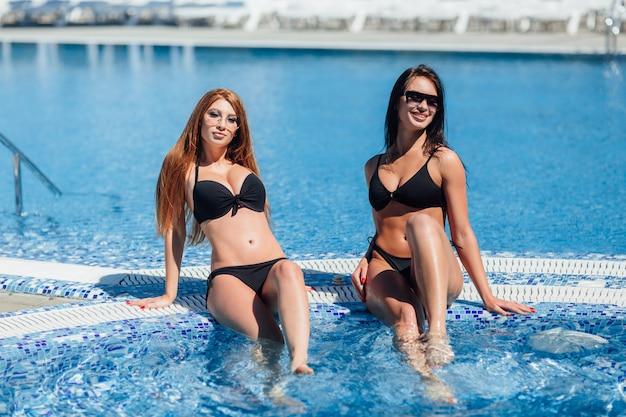 Twee hete vrouwen in zwarte zwemkleding en zonnebril poseren en zonnebaden bij het zwembad. donkerbruin en bruin haar.