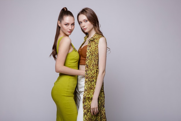 Twee high fashion modellen in robedress broek top schoenen gele salie jurk mooie jonge vrouwen