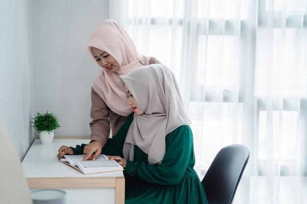Twee hijabvrouwen bestuderen en lezen het heilige boek van al-koran