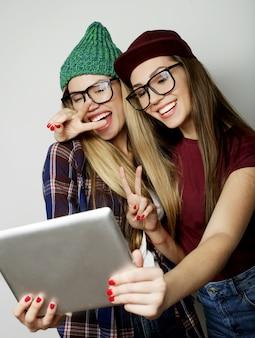 Twee hipster meisjes vrienden nemen selfie met digitale tablet, studio opname op grijze vackground