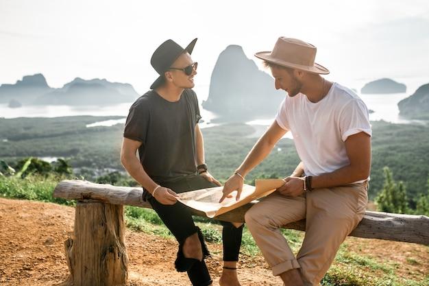 Twee hipster-vrienden reizigers in de hoeden kijken naar de papieren kaart om de juiste manier te vinden. gelukkige hipstermensen die plaats in bergen op landschap onderzoeken. zomer reizen.