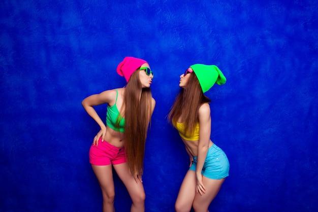 Twee hipsterzusters in kappen en glazen die gaan kussen