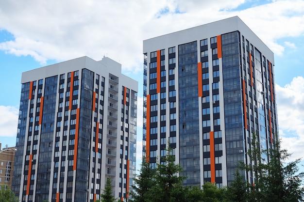Twee hoge woonhuizen op de achtergrond van de heldere hemel