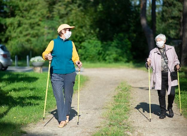 Twee hogere vrouwen die medische maskers dragen die met nordic walking-stokken lopen tijdens covid-19 pandemie
