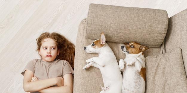 Twee honden slapen op beige bank en ongelukkig meisje liggend op de houten vloer.