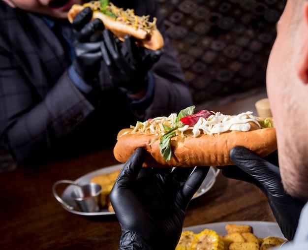 Twee hongerige jonge mannen die hotdogs in koffie eten. restaurant