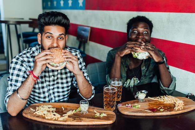 Twee hongerige man die plezier heeft terwijl hij tijd doorbrengt met vrienden in een pub en bier drinkt.