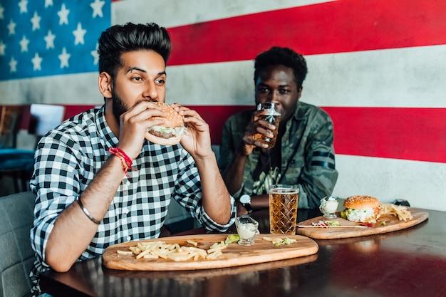 Twee hongerige, zwarte mannen die plezier hebben terwijl ze tijd doorbrengen met vrienden in een pub en bier drinken.
