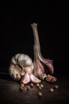 Twee hoofden van knoflook en zwarte peper op een donkere achtergrond