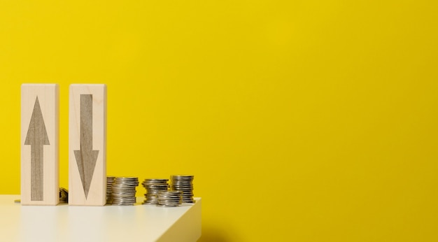 Twee houten balken met pijlen op en neer op de tafel met munten, gele achtergrond. dalingen en stijgingen van de prijzen voor nutsvoorzieningen, wisselkoersen