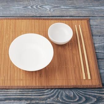 Twee houten eetstokjes en twee witte kom op een bamboe mat