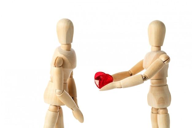 Twee houten figuren van een pop geven een rood hart