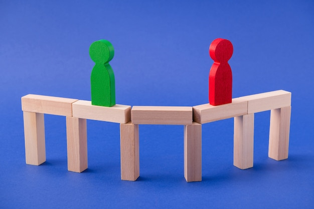 Twee houten figuren, vrienden, leiders, ondernemers, zakenlieden, staande op de brug