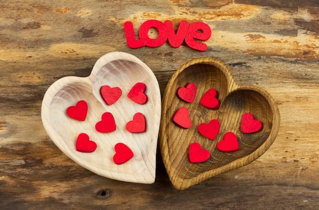 Twee houten harten met binnen kleine rode harten. valentijnsdag. horizontale oriëntatie.