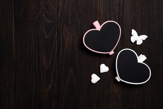 twee houten harten met vlinder op houten achtergrond.