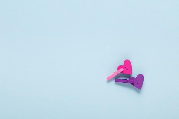 Twee houten harten op wasknijpers op blauw