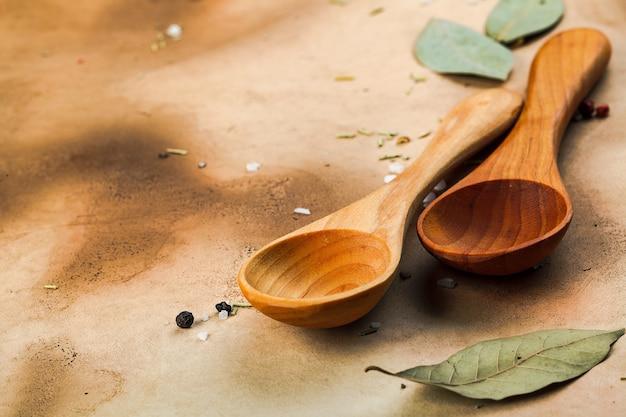 Twee houten lepels, laurierblaadjes, peper en zout op oud middeleeuws papier