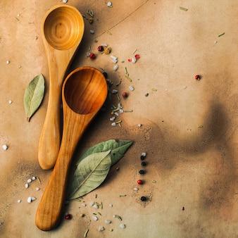 Twee houten lepels, laurierblaadjes, peper en zout
