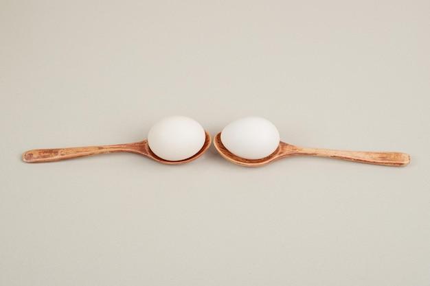 Twee houten lepels met witte kippeneieren.