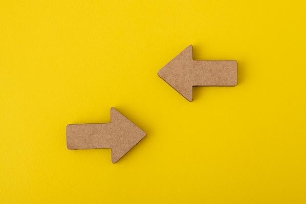 Twee houten pijlen op geel