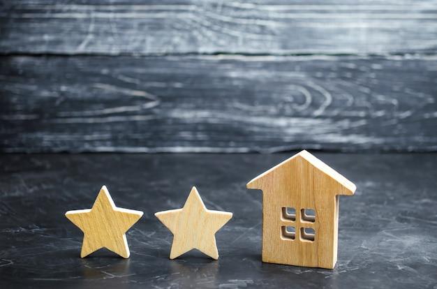 Twee houten sterren en een huis. twee sterren hotel of restaurant. herziening van de criticus.