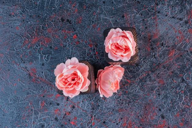 Twee houten stukken met roze bloemen op grijs