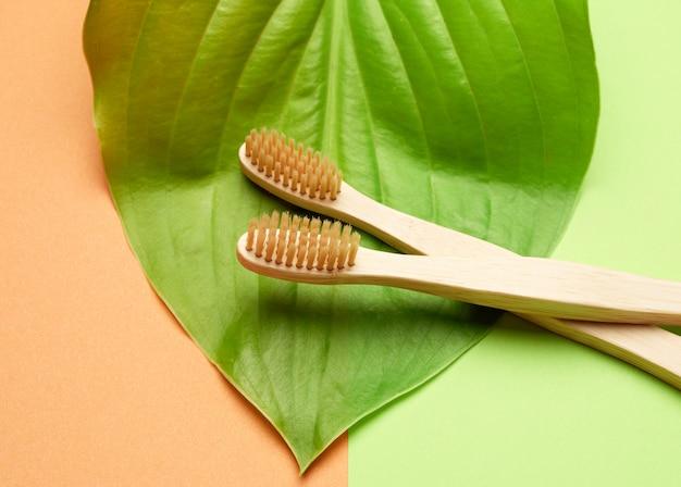 Twee houten tandenborstels op een groenoranje achtergrond, plastic afwijzingsconcept