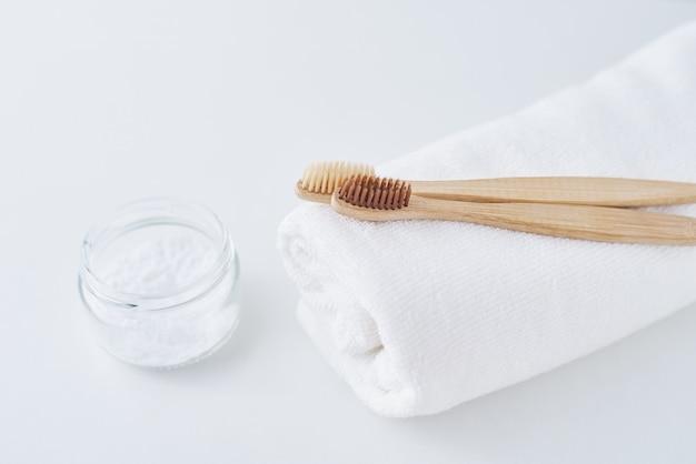 Twee houten vriendschappelijke tandenborstels van bamboeeco op handdoek en zuiveringszout op wit, tandzorgconcept