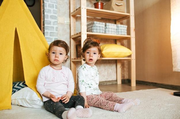 Twee identieke tweelingzusjes zitten op de grond bij de gele tipi van het huis op de vloer. een gelukkig, vriendelijk en vrolijk gezin.