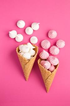 Twee ijshoorntjes met wit en roze schuimgebakje op roze