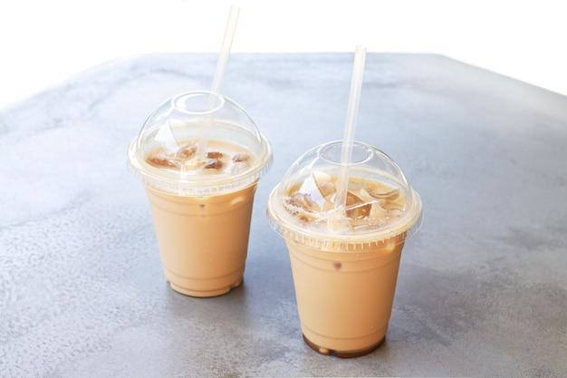 Twee ijskoffie of latte in een plastic beker om mee te nemen op de stenen tafel van het straatcafé