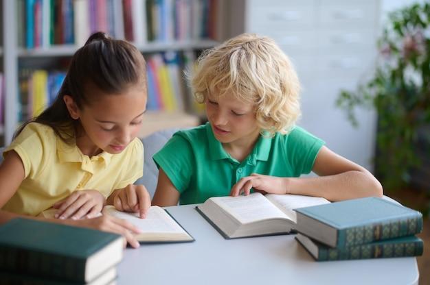 Twee ijverige leerlingen die samen studeren in de bibliotheek