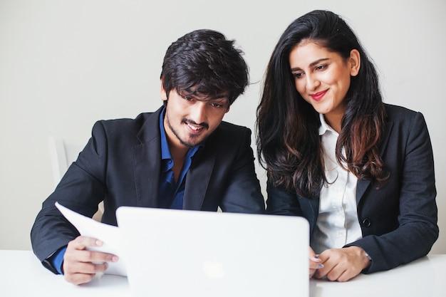 Twee indiase collega's die als een team op een laptop werken