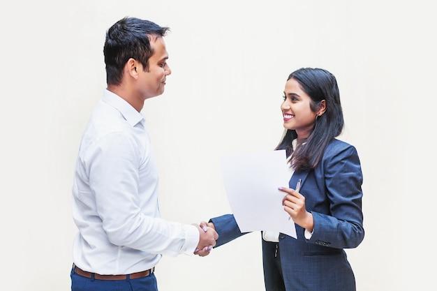 Twee indiase kantoorcollega's die elkaar de hand schudden