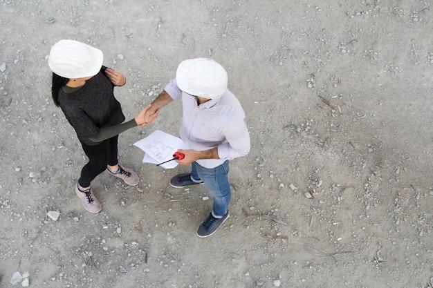 Twee ingenieur handdruk maken in bouw bouwplaats.