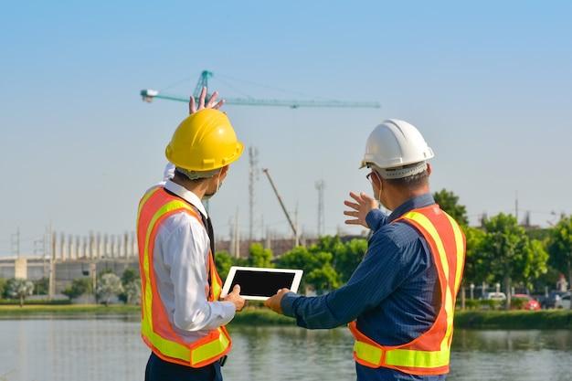 Twee ingenieur werknemer tablet werken op site bouw aziatische man architectuur bouwer gebouw landmeter professional