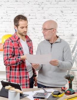 Twee ingenieurs die een plan op kantoor lezen