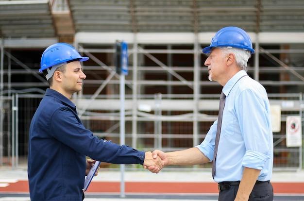 Twee ingenieurs die handen schudden bij een bouwwerf