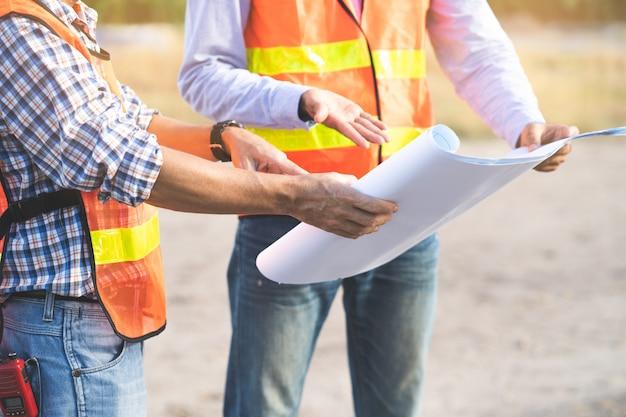 Twee ingenieurs die over blauwdruk van project bespreken.