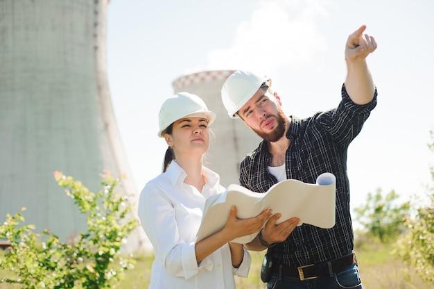 Twee ingenieurs die zich bij elektriciteitspost bevinden, plan bespreken.