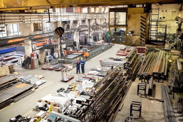 Twee ingenieurs in werkkleding werken samen in een groot industrieel magazijn tussen nieuwe apparatuur